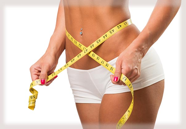 Slim woman measuring her waistline